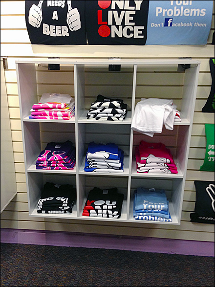 Shelf unit hangs from faceouts fixtures close up retail pop for Retail shirt display ideas
